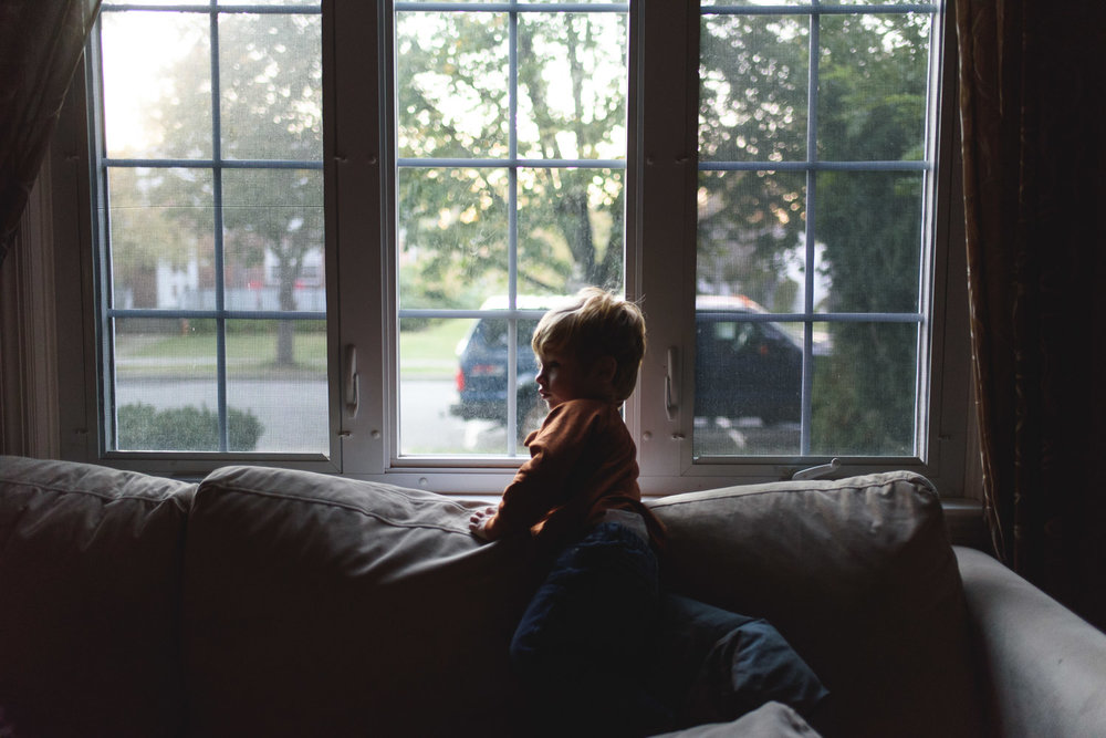 Little boy on couch with big window behind him.
