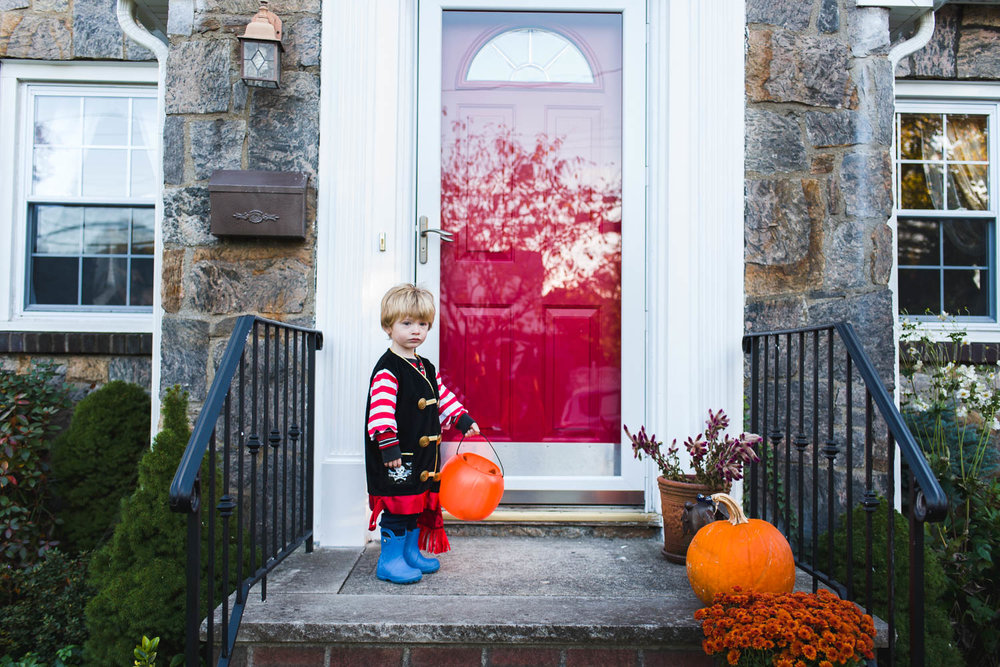Little boy dressed as a pirate goes trick-or-treating.
