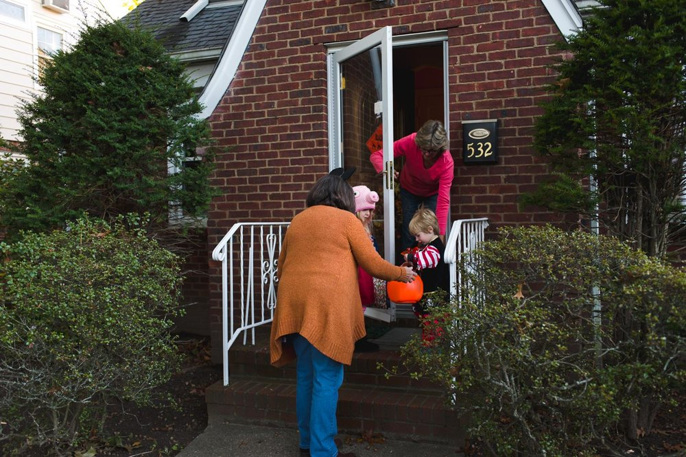 Kids trick-or-treating with grandmother.