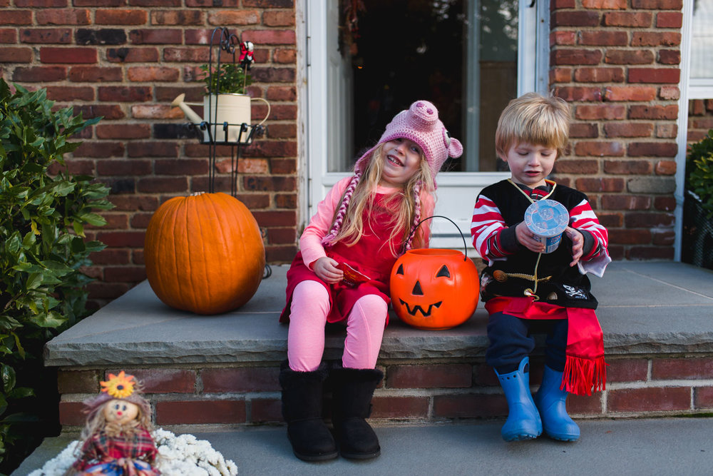 Kids dressed up for Halloween, enjoying their loot.