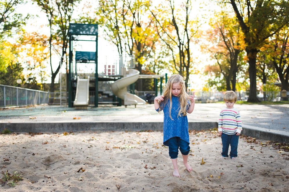 Kids barefoot in the sandbox at the playground.