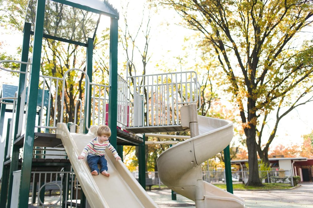 Little boy going down the slide at the playground.