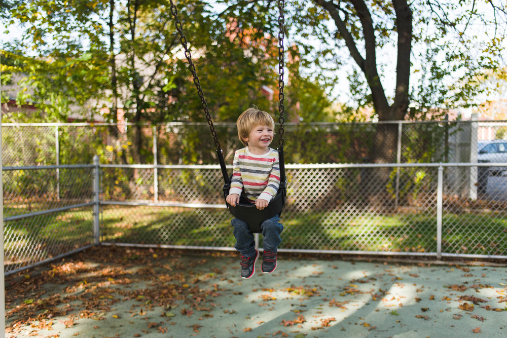 Little boy on a swing at the playground.
