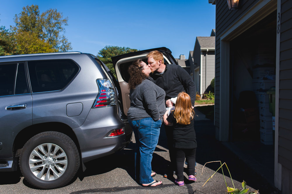 Parents exchange a kiss in the driveway.