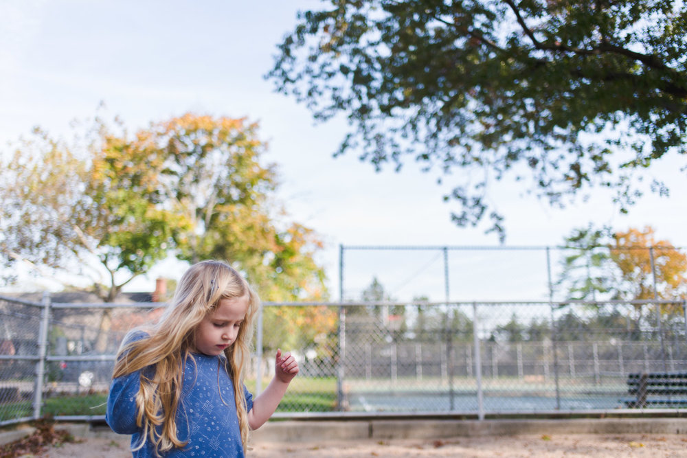 Little girl with blonde hair walking through the park.