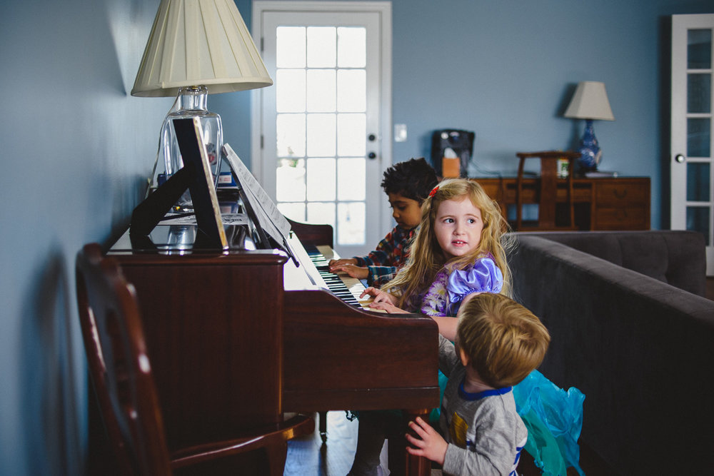 Kids sitting together playing the piano.