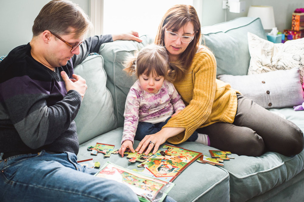Family playing a board game on the couch.