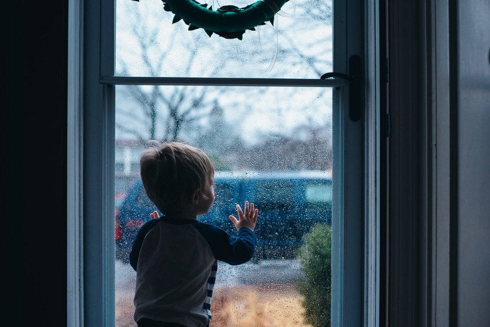 Little boy watching the rain outside.
