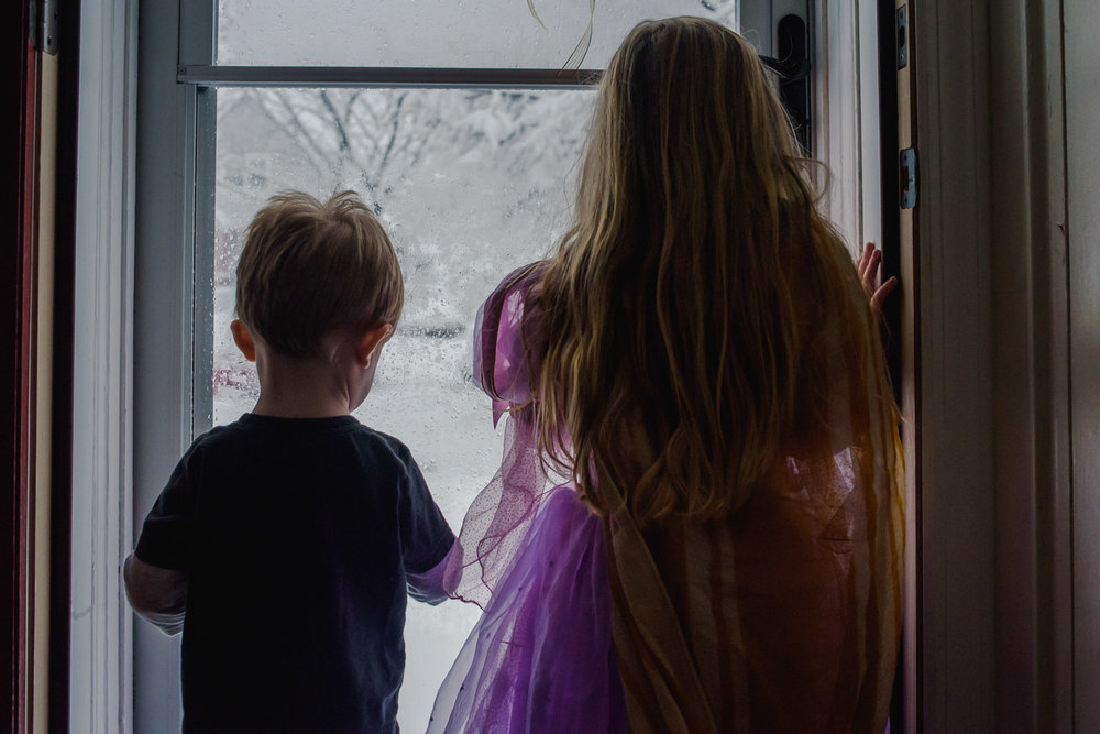 Brother and sister watching the snow fall.