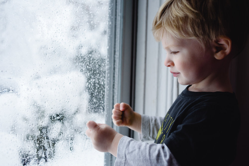 Little boy watching the snow fall.