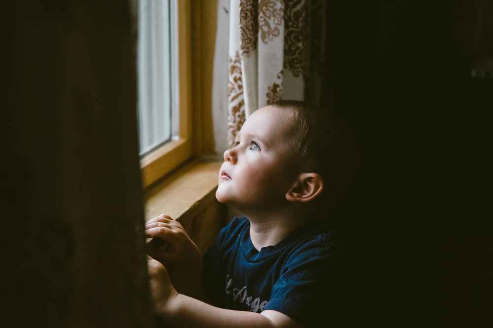 Little boy looking out window.