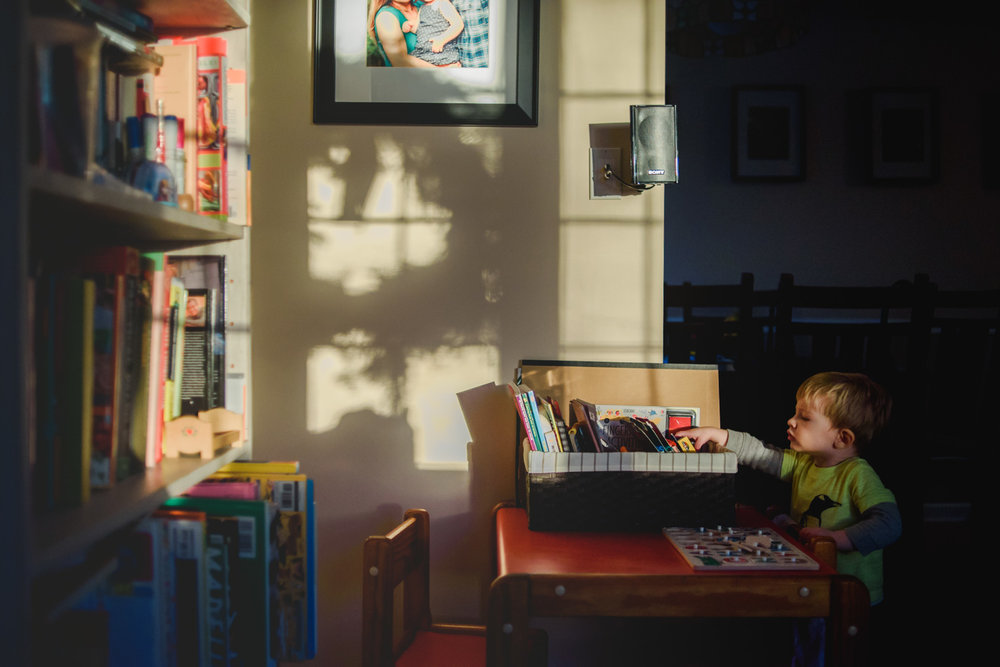 Little boy in living room with deep afternoon shadows.