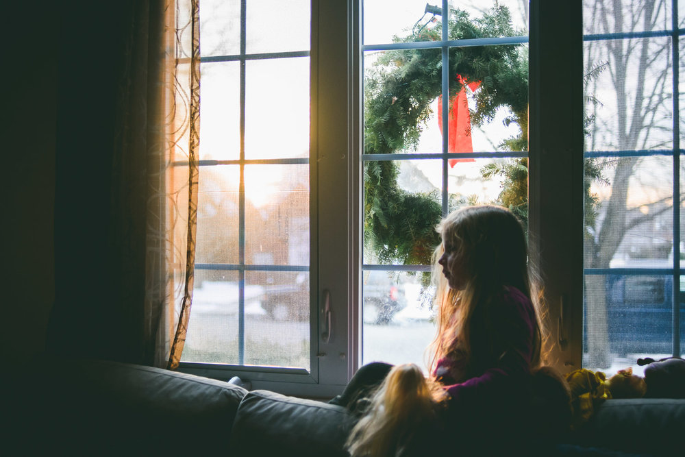 Little girl perched on couch during winter golden hour.