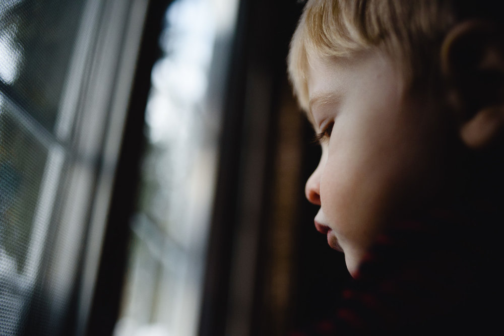 Little boy next to window.