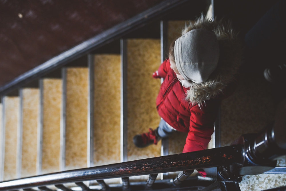 Child in winter clothes descends stairs.