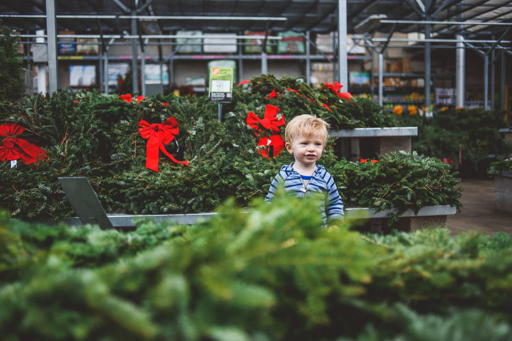 Little boy amidst wreaths at Home Depot.