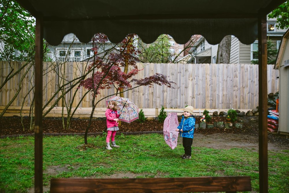 Kids in backyard with umbrella.