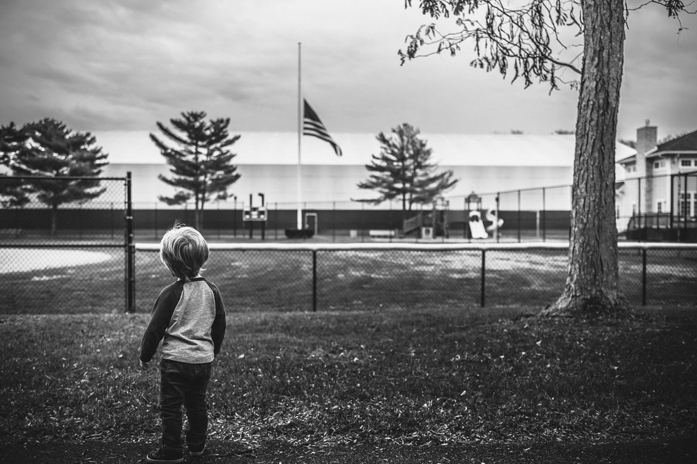 Little boy at park looking at the American flag.