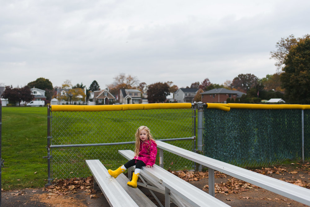 Little girl sitting on bleachers.