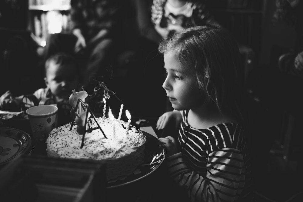 Little girl blowing out candles on cake.