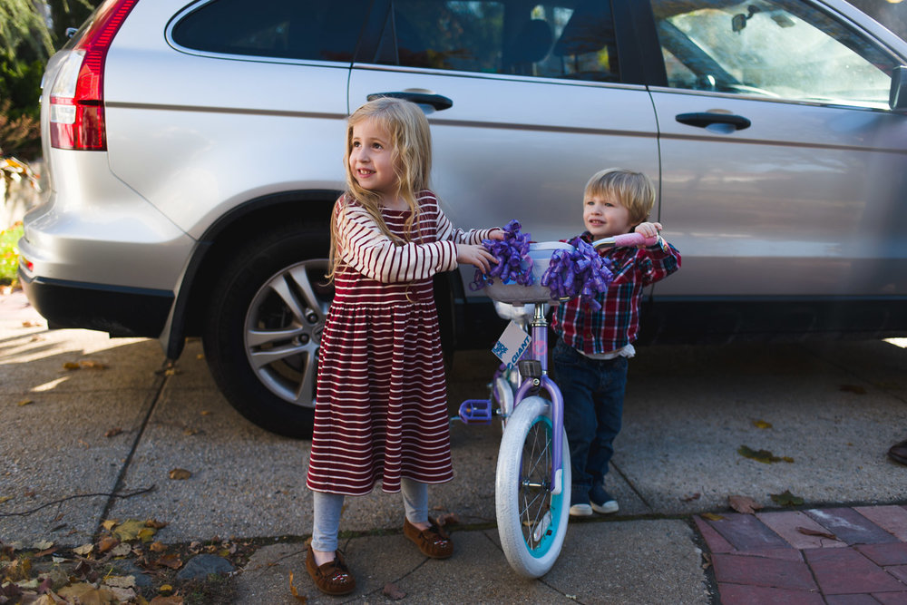 Little girl proudly showing off her first two-wheeler bike.