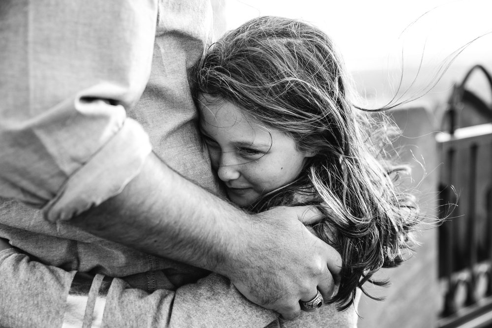 A girl embracing her father.