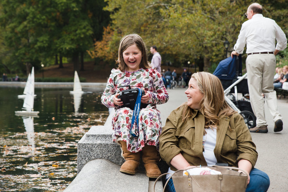 Mother and daughter operating a model boat at Conservatory Waters in Central Park.