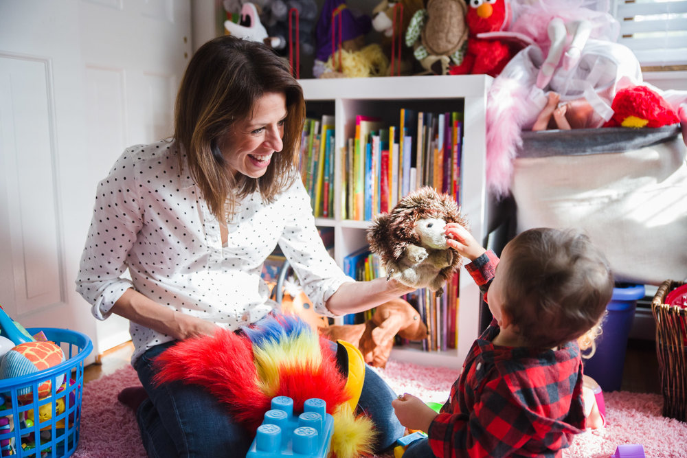 Mother playing puppets with toddler.