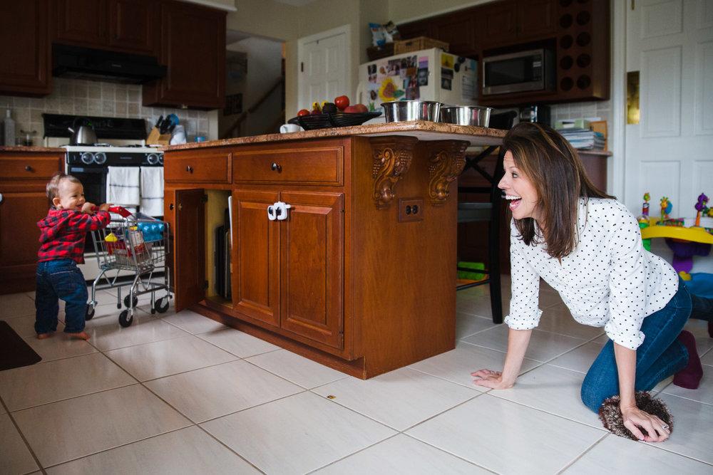 Mother chasing toddler around kitchen island.