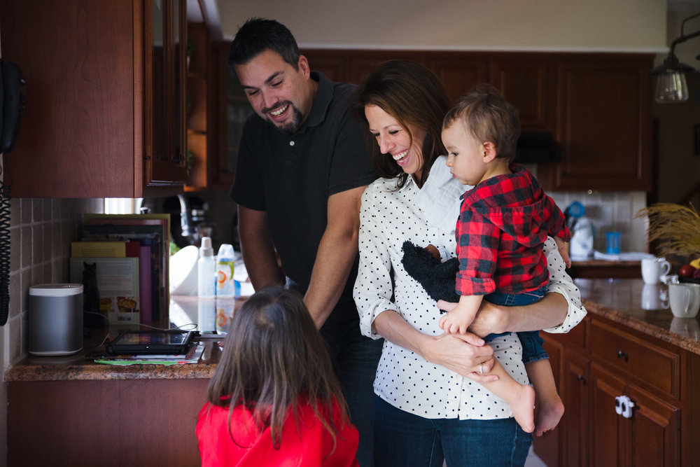 Family gathered in the kitchen, smiling.