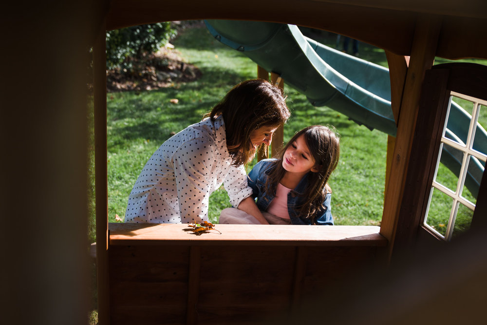 Mother and daughter talking in playhouse.