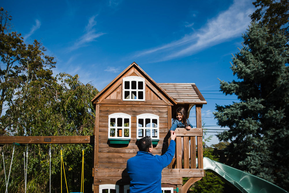 Dad and daughter playing in playhouse.