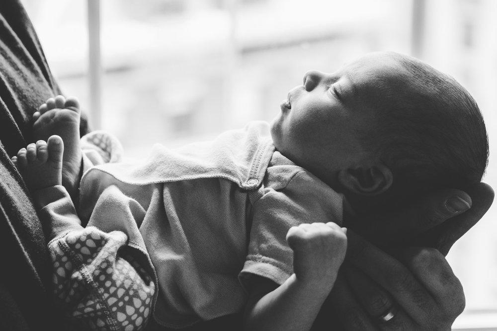Newborn baby held in father's hands.