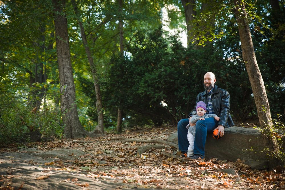 Father and daughter sitting on a rock in Riverside Park.