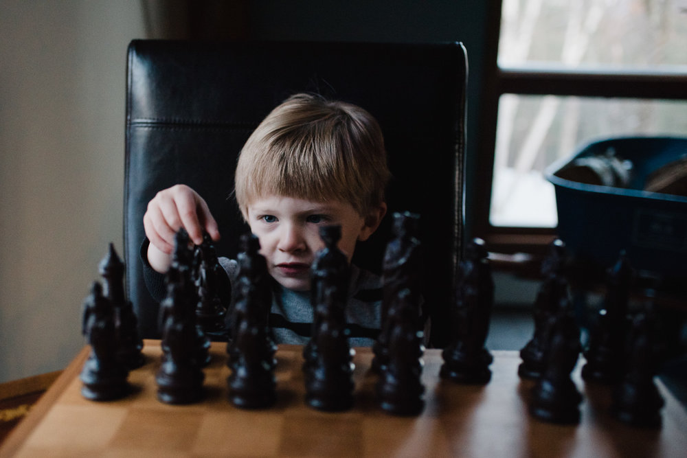 Little boy playing chess.