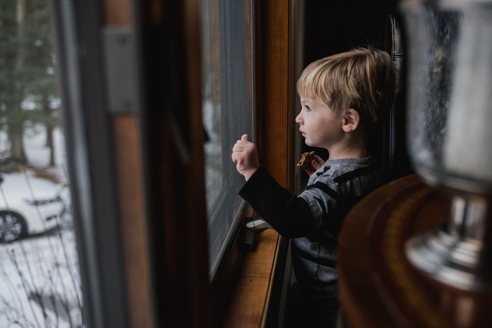 Little boy knocking on a window.