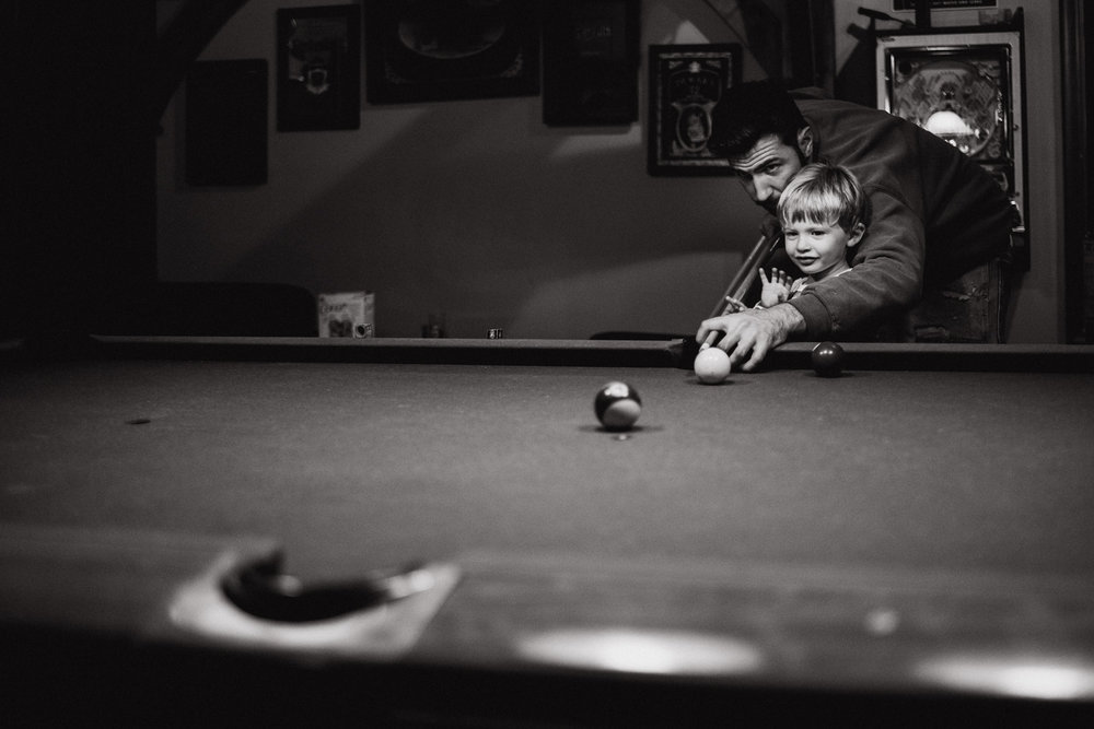 Father and toddler son playing pool.