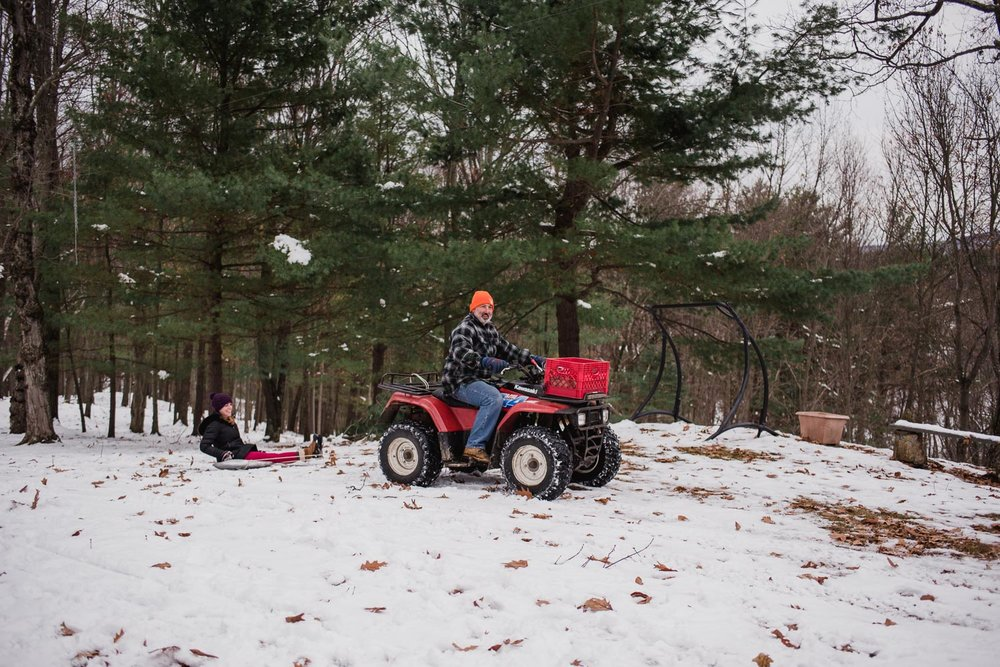 Kelsey getting a ride through the snow on a saucer pulled by the four wheeler.