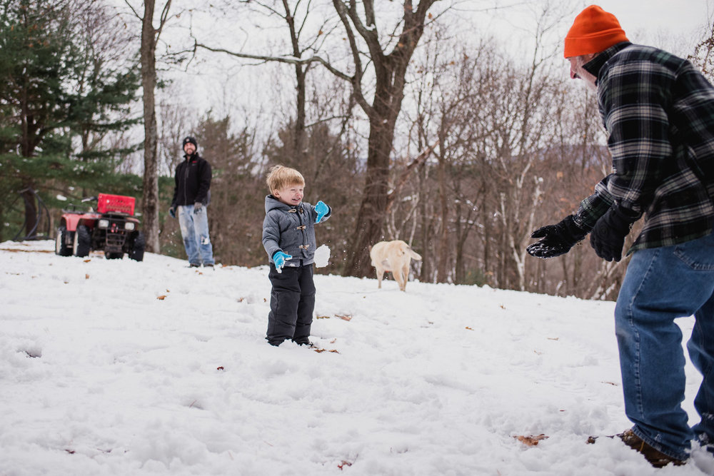 Little boy getting hit by a snowball.