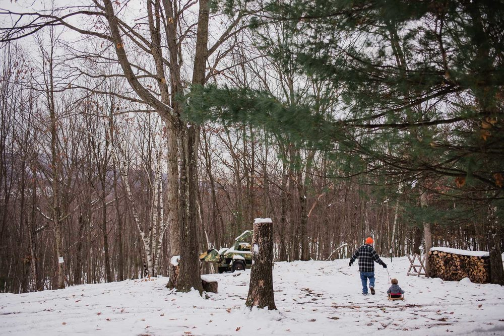A little boy goes sledding with his grandfather.