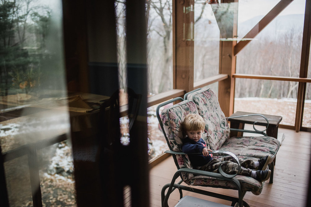 Little boy sitting on porch swing.