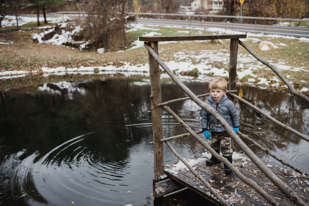 Little boy on a pier at a pond.