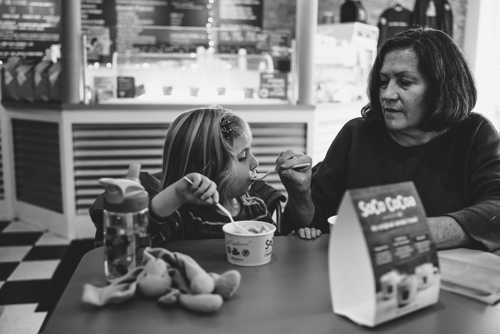 Grandmother and granddaughter eat ice cream at SoCo creamery.