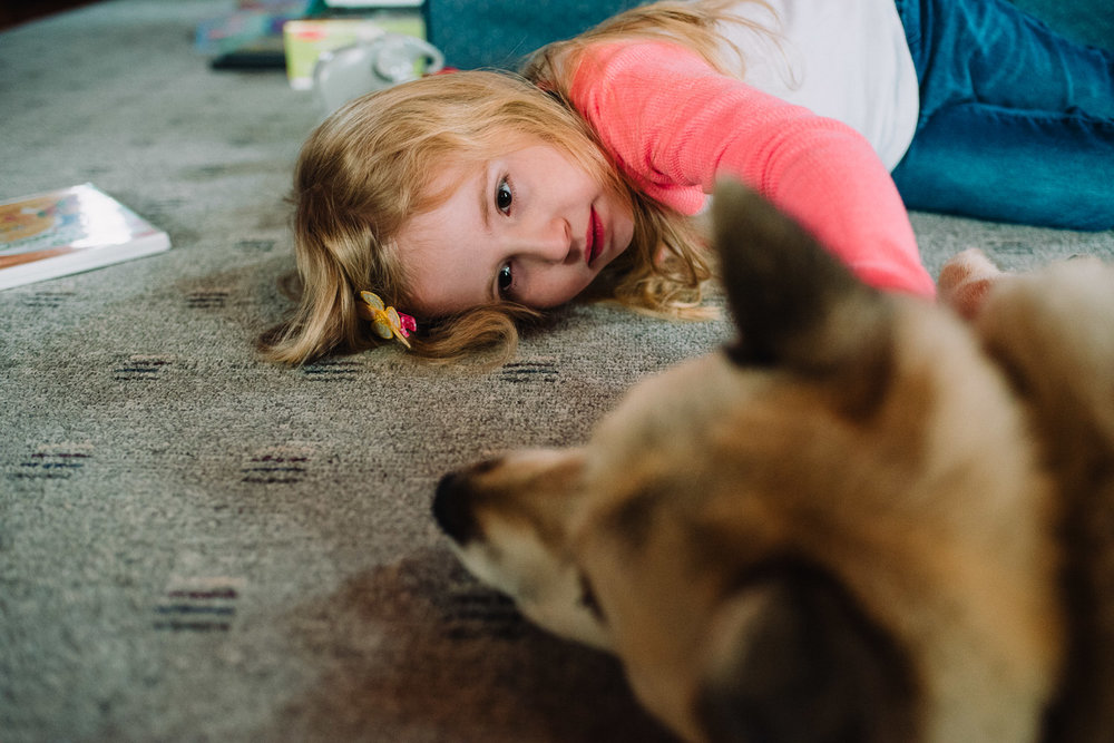 Little girl lying on floor with dog.