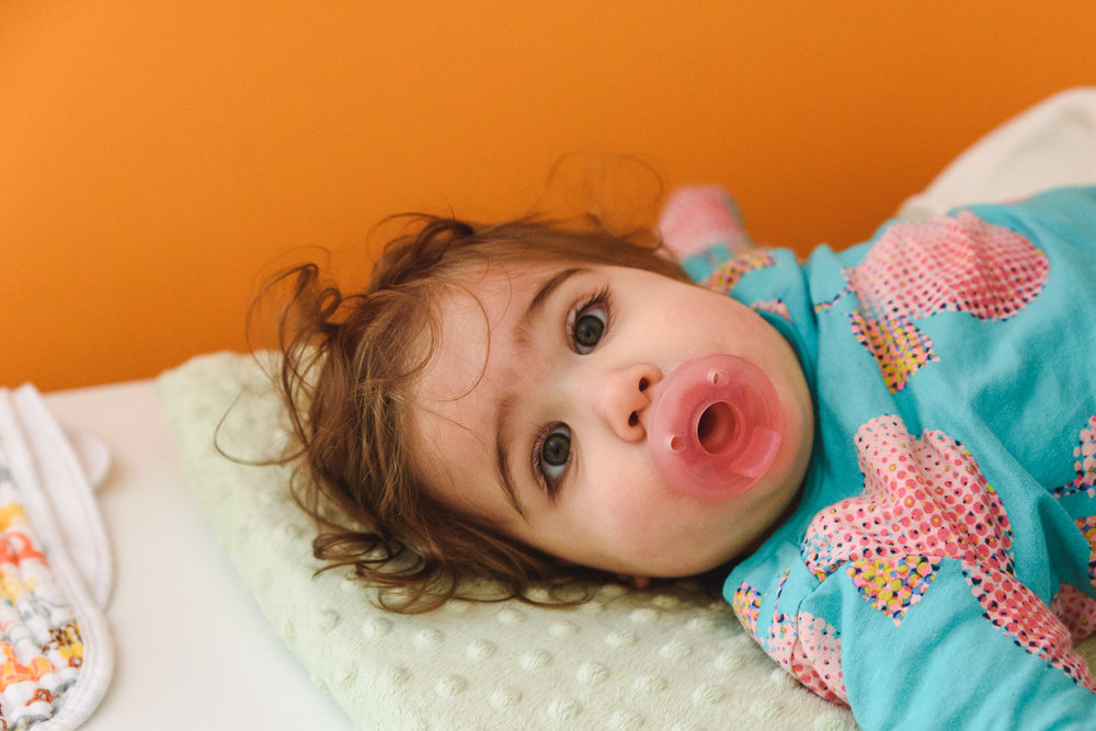 Toddler lying down with pacifier in mouth.