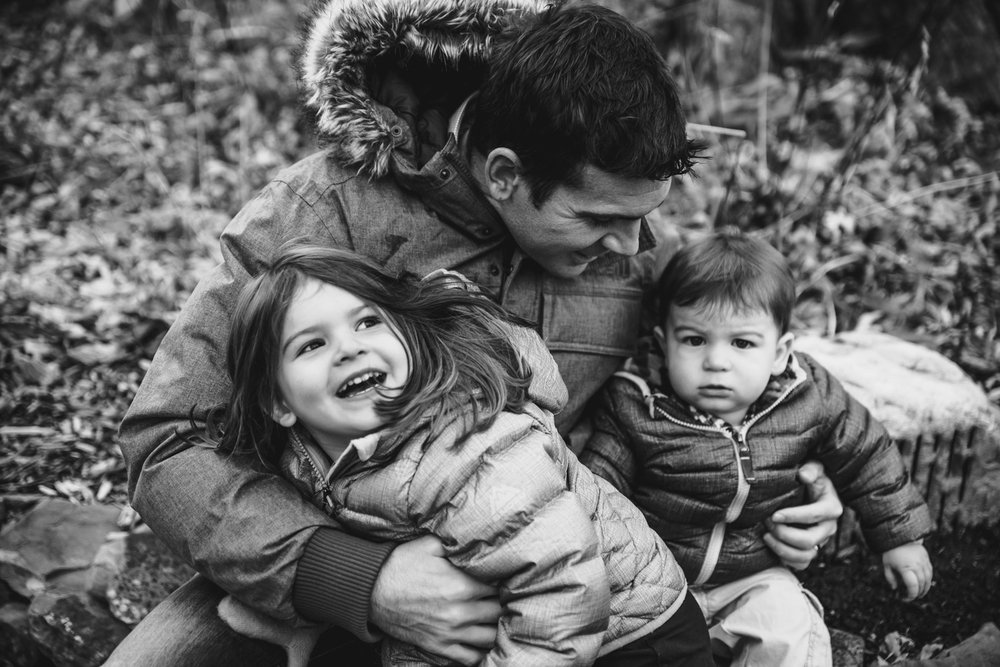 A father embraces his two young children outdoors.
