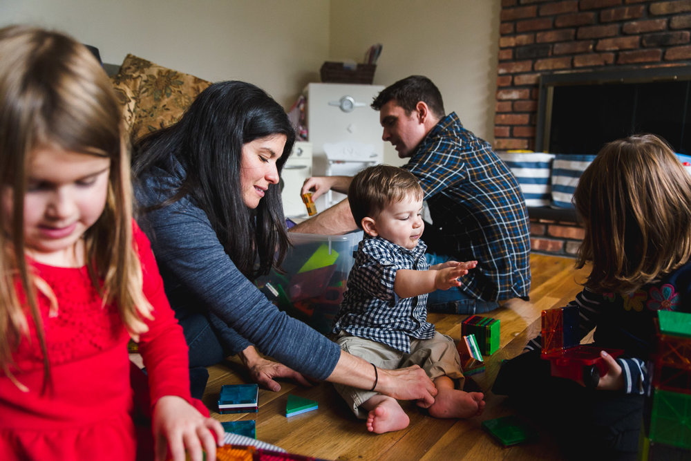 A family with young children plays with magna tiles in their living room.