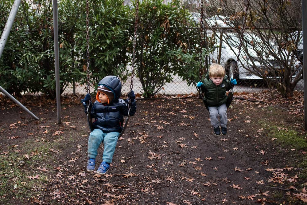 Toddler boys swinging on swings.