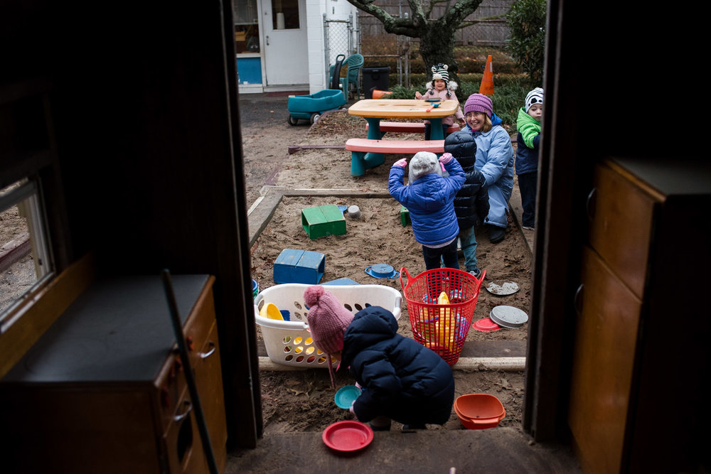 Kids playing in the sandbox at nursery school.