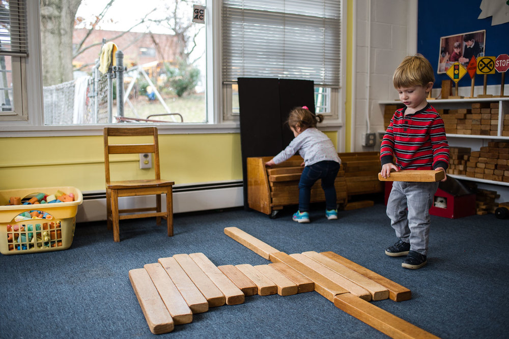 A little boy builds a structure out of blocks at his nursery school.